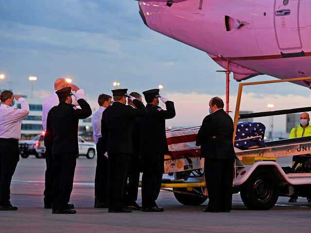 Ambulnz paramedics and Aurora firefighters salute as the casket carrying the body of paramedic Paul Cary is removed from a plane at Denver International Airport on Sunday, May 3, 2020, in Denver. Cary died from coronavirus after volunteering to help combat the pandemic in New York City. (Helen H. Richardson/The …