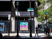 People pass newly installed posters on a shuttered businesses in Philadelphia, Monday, May 4, 2020. The Center City District and Mural Arts Philadelphia posted the original works on multiple locations in an effort to enhance the neighborhood awash with business shuttered to help curb the spread of coronavirus. (AP Photo/Matt …