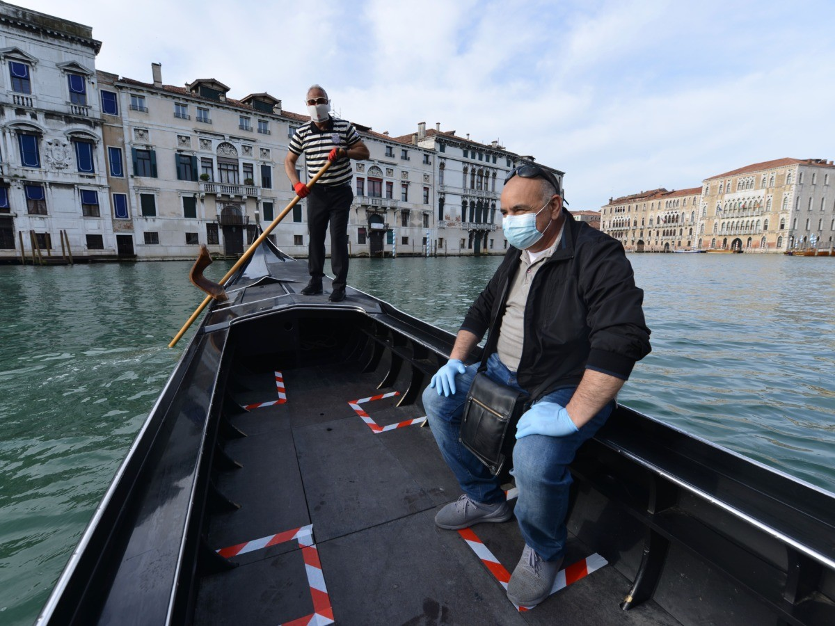 A gondolier (Rear) wearing a face mask resumes service on a Venice canal on May 18, 2020 during the country's lockdown aimed at curbing the spread of the COVID-19 infection, caused by the novel coronavirus. - Restaurants and churches reopen in Italy on May 18, 2020 as part of a fresh wave of lockdown easing in Europe and the country's latest step in a cautious, gradual return to normality, allowing businesses and churches to reopen after a two-month lockdown. (Photo by ANDREA PATTARO / AFP) (Photo by ANDREA PATTARO/AFP via Getty Images)
