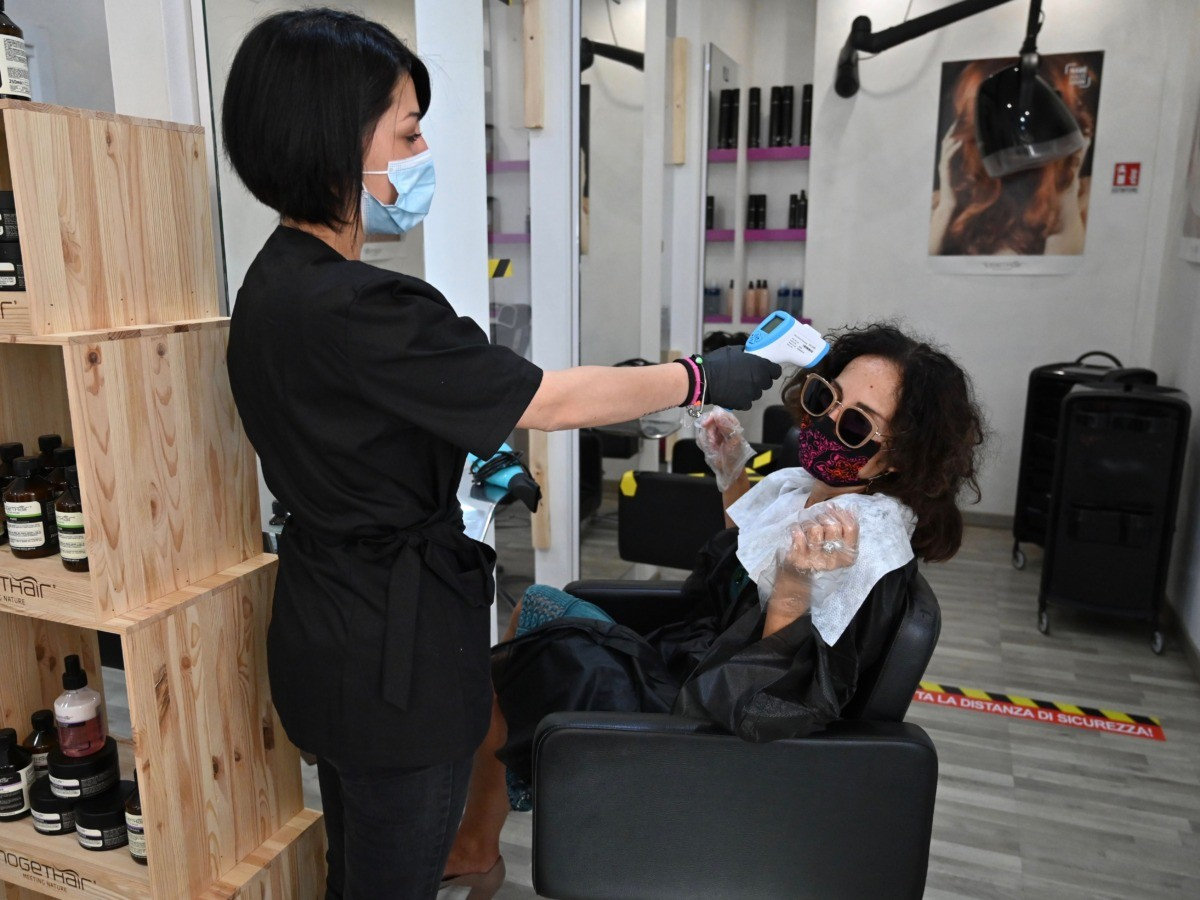 A woman undergoes a body temperature scanning at a hairdresser's saloon in Rome on May 18, 2020 during the country's lockdown aimed at curbing the spread of the COVID-19 infection, caused by the novel coronavirus. - Restaurants and churches reopen in Italy on May 18, 2020 as part of a fresh wave of lockdown easing in Europe and the country's latest step in a cautious, gradual return to normality, allowing businesses and churches to reopen after a two-month lockdown. (Photo by ANDREAS SOLARO / AFP) (Photo by ANDREAS SOLARO/AFP via Getty Images)