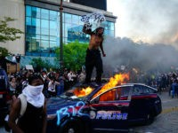 ATLANTA, GA - MAY 29: A man stands on top of a burning police car during a protest on May 29, 2020 in Atlanta, Georgia. Demonstrations are being held across the US after George Floyd died in police custody on May 25th in Minneapolis, Minnesota. (Photo by Elijah Nouvelage/Getty Images)