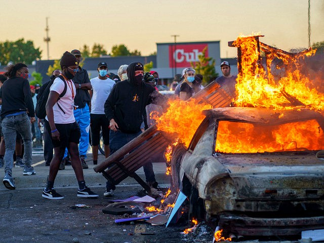 Protesters throw objects onto a burning car outside a Target store near the Third Police Precinct on May 28, 2020 in Minneapolis, Minnesota, during a demonstration over the death of George Floyd, an unarmed black man, who died after a police officer kneeled on his neck for several minutes. - …