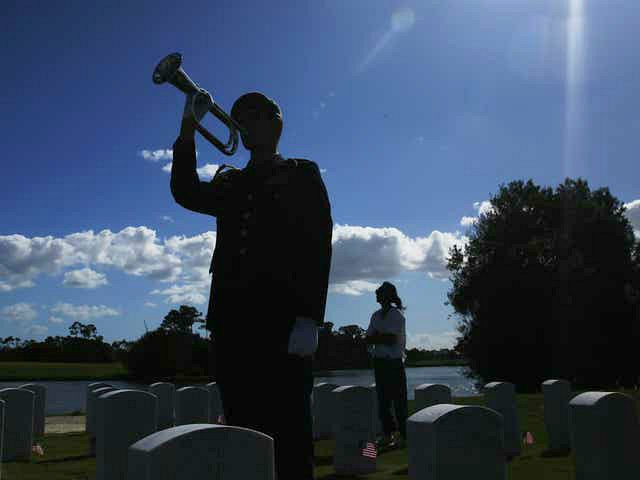"A member of the military plays ""Taps"" for a family member during a flag ceremony at the South Florida National Cemetery on Veterans Day on Sunday, Nov. 10, 2019, in Lake Worth, Fla. (AP Photo/Brynn Anderson)"