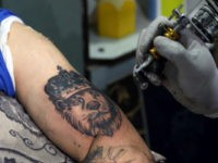 In this Wednesday, Nov. 20, 2019, photo, Omid Noori, 23, left, gets a lion tattoo on his left arm by Nazeer Mosawi, a tattoo artist in Kabul, Afghanistan. Mosawi, 42, fought for seven years in Afghanistan's civil war with the Islamic insurgents. He says he is still fighting the war, …