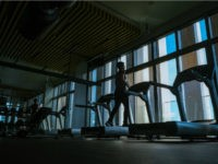 Man running on treadmill in a dark fitness center