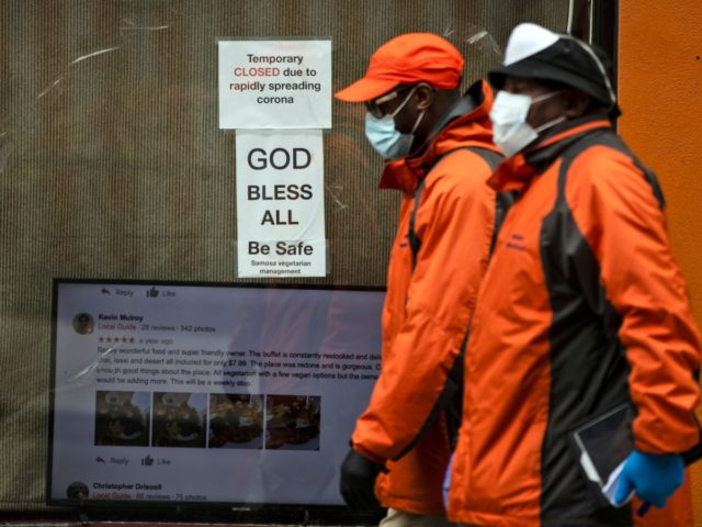 """Pedestrians in protective face mask walk past a closed business in Philadelphia, Friday, March 20, 2020. Pennsylvania Gov. Tom Wolf directed all """"non-life-sustaining"""" businesses to close their physical locations late Thursday and said state government would begin to enforce the edict starting early Saturday. (AP Photo/Matt Rourke)"""