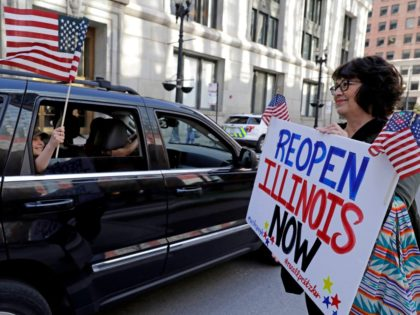 Protesters rally against Illinois stay-at-home order outside the Thompson Center in downtown Chicago, Friday, May 1, 2020. The Friday demonstration is the latest in a series of protests around the country against stay-at-home orders designed to slow the spread of the coronavirus. (AP Photo/Nam Y. Huh)