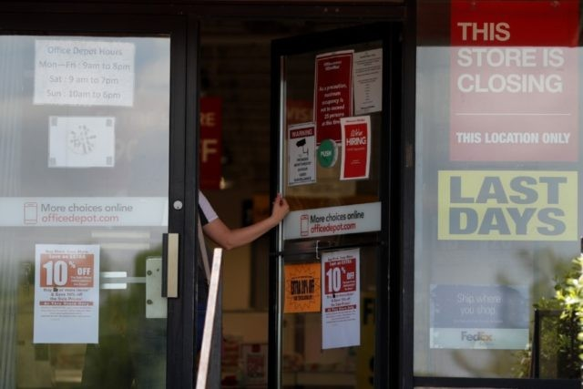 A person walks into an office supply retailer that is closing that location Thursday, May 7, 2020, in Olivette, Mo. (AP Photo/Jeff Roberson)