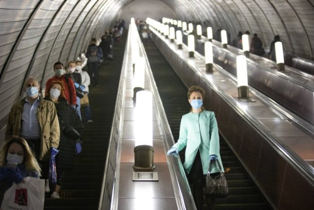 People wearing face masks and gloves to protect against coronavirus, observe social distancing guidelines as they go down the subway on the escalator in Moscow, Russia, Tuesday, May 12, 2020. From Tuesday onward, wearing face masks and latex gloves is mandatory for people using Moscow's public transport. President Vladimir Putin …