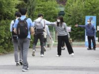 A senior student is greeted by a teacher, second from right, upon his arrival at the Kyungbock High School in Seoul, South Korea, Wednesday, May 20, 2020. South Korean high schools reopened on Wednesday after weeks of postponement due to safety concerns over the coronavirus outbreak. (AP Photo/Ahn Young-joon)