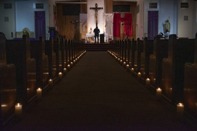 In this April 11, 2020, file photo, a person films pastor Nicolas Sanchez, center left, celebrating Easter Vigil Mass at his church decorated with candles and pictures sent by his parishioners attached to their pews at St. Patrick Church in North Hollywood, Calif. The head of the federal Justice Department's …