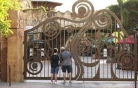 In this Thursday, May 14, 2020, file photo, guests peer through the closed gate to Universal's Islands of Adventure beside Universal CityWalk, in Orlando, Fla. Universal Orlando is aiming to reopen its theme parks in early June, a resort official said Thursday, May 20, more than two months after the …