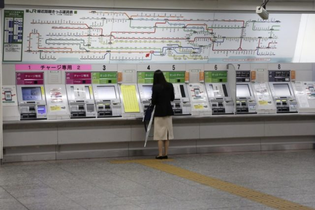 A woman buys a train ticket at quiet Yokohama station in Yokohama, Kanagawa prefecture, near Tokyo, Thursday, May 21, 2020. Kanagawa is still under a coronavirus state of emergency until the end of May, though there have been no hard lockdowns. (AP Photo/Koji Sasahara)