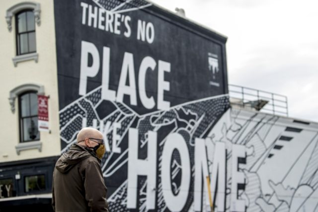"""In this April 14, 2020, file photo, a mural that reads """"There's No Place Like Home"""" is visible as a man wearing a mask crosses 14th Street in Washington. As a candidate for the White House, President Donald Trump once said he wanted """"whatever is best"""" for the residents of …"""