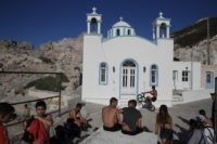 Children gather in front of a Greek Orthodox church on the Aegean Sea island of Milos, Greece, on Sunday, May 24, 2020. Greece's long-awaited tourist season will begin on June 15 with the opening of seasonal hotels and the arrival of the first foreign visitors, while international flights will begin …