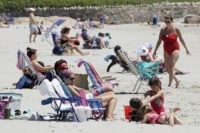Beachgoers relax on the shore at Good Harbor Beach in Gloucester, Mass., Friday, May 22, 2020. Beaches in Gloucester reopened with restrictions on Friday after being closed two months ago due to the pandemic. (AP Photo/Charles Krupa)