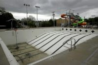 In this photo taken Friday, May 15, 2020, the public pool in Mission, Kan. is lifeless as plans remain in place to keep the pool closed for the summer to help prevent the spread of COVID-19. As warm weather approaches and many public pools remain closed there has been a …