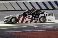 Brad Keselowski holds an American flag after winning the NASCAR Cup Series auto race at Charlotte Motor Speedway early Monday, May 25, 2020, in Concord, N.C. (AP Photo/Gerry Broome)