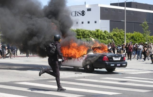 A person runs while a police vehicle is burning during a protest over the death of George Floyd in Los Angeles, Saturday, May 30, 2020. Protests across the country have escalated over the death of George Floyd who died after being restrained by Minneapolis police officers on Memorial Day, May …