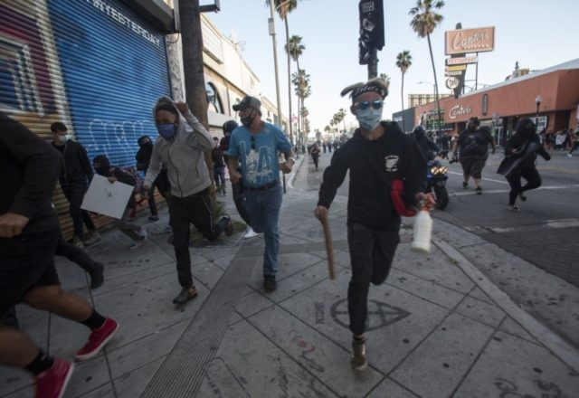 Protesters run as police officers fire rubber bullets during a protest over the death of George Floyd, a handcuffed black man in police custody in Minneapolis, in Los Angeles, Saturday, May 30, 2020. (AP Photo/Ringo H.W. Chiu)