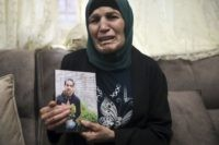 Rana, mother of Iyad Halak, 32, holds his photo at their home in East Jerusalem's Wadi Joz, Saturday, May 30, 2020. Israeli police shot dead a Palestinian near Jerusalem's Old City who they had suspected was carrying a weapon but turned out to be unarmed. A relative said Halak was …