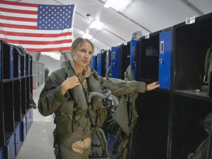 U.S. Air Force Capt. Emily Thompson, 421st Expeditionary Fighter Squadron pilot, dons flight equipment at the Aircrew Flight Equipment shop on Al Dhafra Air Base, United Arab Emirates, June 5, 2020. Thompson is the first female to fly an F-35A Lightning II into combat. She is currently deployed from Hill …