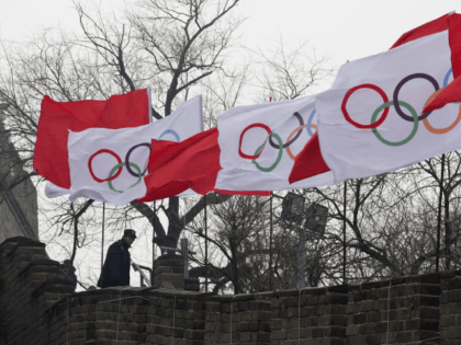 A security person stands near the Olympic flags during a ceremony to mark the arrival of the Olympic flag and start of the flag tour for the Winter Olympic Games Beijing 2022 at a section of the Great Wall of China in Beijing Tuesday, Feb. 27, 2018. (AP Photo/Ng Han …