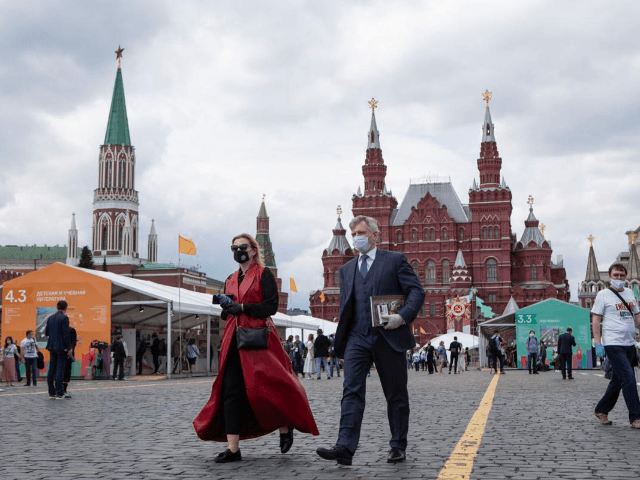 People wearing face masks to protect against coronavirus walk an outdoor book market set up in Red Square with a Historical museum in the background in Moscow, Russia, on Saturday, June 6, 2020. Muscovites clad in face masks and gloves ventured into Red Square for an outdoor book market, a …