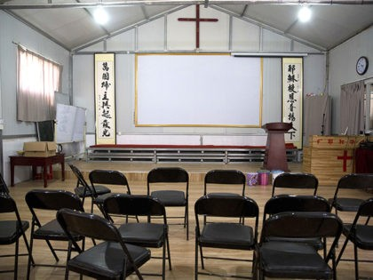 "In this photo taken Monday, June 4, 2018, Chinese calligraphy which reads ""All nations belong to the Lord arising to shine"" at left and ""Jesus's salvation spreads to the whole world"" at right are displayed below a crucifix in a house church shut down by authorities near the city of …"