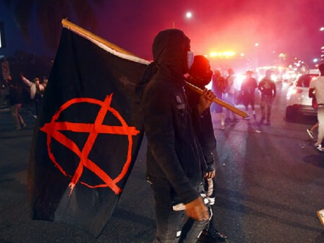 A man carries a flag depicting the anarchist symbol during a public disturbance on Melrose Avenue, Saturday, May 30, 2020, in Los Angeles. Protests were held in U.S. cities over the death of George Floyd, a black man who died after being restrained by Minneapolis police officers on May 25. …