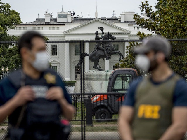 The White House is visible behind a large security fence as uniformed Secret Service and FBI agents stand on the street in front of Lafayette Park in the morning hours in Washington, Tuesday, June 2, 2020, as protests continue over the death of George Floyd. Floyd died after being restrained …
