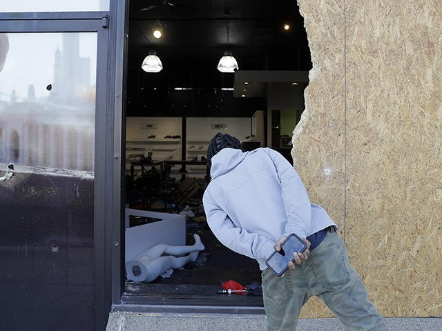 A man looks into a burglarized and ransacked business Tuesday, June 2, 2020, in St. Louis. People were seen removing merchandise from the business on Monday night well after peaceful protesters gathered in the afternoon to speak out against the death of George Floyd who died after being restrained by …