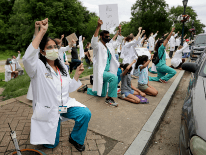 Healthcare professionals gather outside Barnes-Jewish Hospital to demonstrate in support of the Black Lives Matter movement Friday, June 5, 2020, in St. Louis, Mo. The White Coats for Black Lives protest was organized to stand in solidarity with those speaking out against the death of George Floyd who died after …