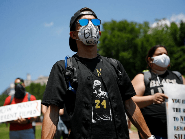 Protesters wear face masks to protect against the spread of the new coronavirus as they gather in Lafayette Square, Saturday, June 13, 2020, near the White House in Washington, while demonstrating against the death of George Floyd. (AP Photo/Patrick Semansky)