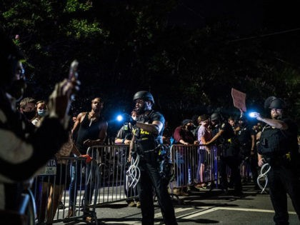 Police flash a light on the protestors during a protest to mark Juneteenth in Atlanta, Georgia on June 19, 2020. - The US marks the end of slavery by celebrating Juneteenth, with the annual unofficial holiday taking on renewed significance as millions of Americans confront the nation's living legacy of …