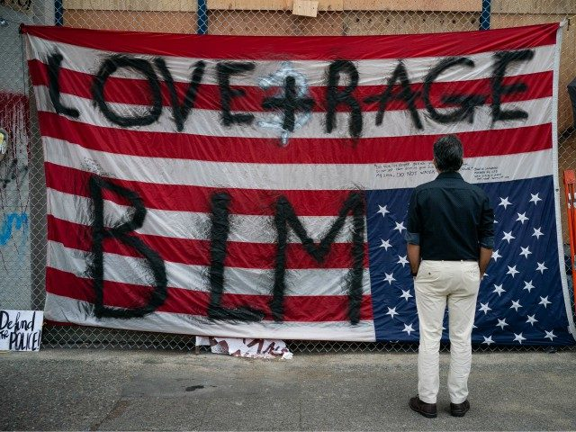 """SEATTLE, WA - JUNE 14: A man views an upside down U.S flag at the Seattle Police Departments vacated East Precinct during ongoing Black Lives Matter events in the so-called Capitol Hill Organized Protest"""" area on June 14, 2020 in Seattle, Washington. Black Lives Matter protesters have continued demonstrating in …"""