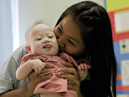 """Thai surrogate mother Pattaramon Chanbua (back) plays with her baby Gammy, born with Down Syndrome, at the Samitivej hospital, Sriracha district in Chonburi province on August 4, 2014. The surrogate mother of a baby reportedly abandoned by his Australian parents in Thailand because he has Down Syndrome was a """"saint"""" …"""
