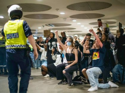 Protesters kneel and raise fists in front of police officers at a subway station during a Black Lives Matter demonstration in Stockholm, Sweden, on June 3, 2020, in solidarity with protests raging across the United States over the death of George Floyd. - Former Minneapolis police officer Derek Chauvin, who …