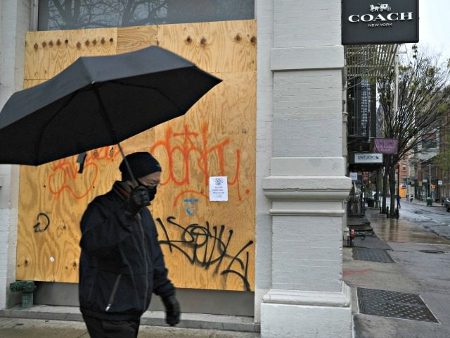 NEW YORK, NY - APRIL 26: A person walks past a boarded-up business in the popular Manhattan shopping district of SoHo on April 26, 2020 in New York City. New York City, which has been the hardest hit city in America from COVID-19, is starting to see a slowdown in …