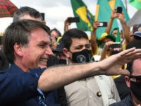 Brazil's President Jair Bolsonaro greets supporters upon arrival at Planalto Palace in Brasilia, on May 24, 2020, amid the COVID-19 coronavirus pandemic. Despite positive signs elsewhere, the disease continued its surge in large parts of South America, with the death toll in Brazil passing 22,000 and infections topping 347,000, the …