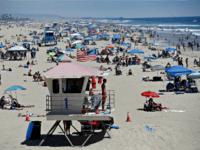 In this June 27, 2020, file photo, a lifeguard keeps watch over a packed beach in Huntington Beach, Calif. The Los Angeles County Department of Public Health is ordering L.A. County beaches closed from July 3 through July 6 at 5:00 a.m. to prevent dangerous crowding that results in the …