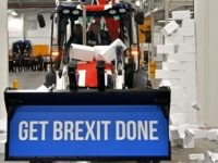 "UTTOXETER, ENGLAND - DECEMBER 10: Britain's Prime Minister and Conservative party leader Boris Johnson drives a Union flag-themed JCB, with the words ""Get Brexit Done"" inside the digger bucket, through a fake wall emblazoned with the word ""GRIDLOCK"", during a general election campaign event at JCB construction company on December …"