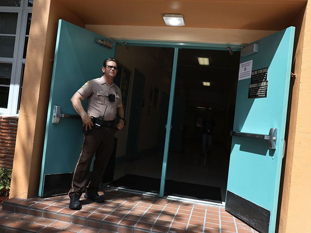 MIAMI, FL - AUGUST 24: Germany Alech, a Miami-Dade Police officer, stands guard at the front entrance to the Kenwood K-8 Center on August 24, 2018 in Miami, Florida. Miami-Dade County Mayor Carlos A. Gimenez and Miami-Dade County Public Schools Superintendent Alberto Carvalho visited the school and were briefed by …