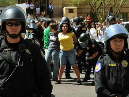 Anti-SB1070 protesters are arrested after staging a sit-in and blocking 1st Avenue in downtown Phoenix on July 29, 2010. Protestors and police in riot gear clashed in several downtown locations with demonstrations against a new Arizona immigration law just hours after it went into effect. Demonstrators angrily denounced the law, …