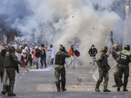 "TOPSHOT - Riot police clash with opposition demonstrators during a protest against the government of President Nicolas Maduro on the anniversary of the 1958 uprising that overthrew the military dictatorship, in Caracas on January 23, 2019. - Venezuela's National Assembly head Juan Guaido declared himself the country's ""acting president"" on …"