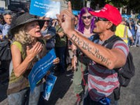 """A supporter of President Trump disrupts members of the Jewish community as they hold a """"Jews Say #CloseTheCamps"""" protest and vigil to demand an end to the Trump administration's detention of migrants, refugees and asylum seekers, outside the Metropolitan Detention Center in Los Angeles, California on August 11, 2019. (Photo …"""