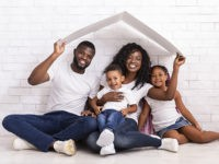 Family Housing Concept. Young African American Parents With Two Children Sitting Under Cartboard Roof Dreaming Of New Home, Copy Space