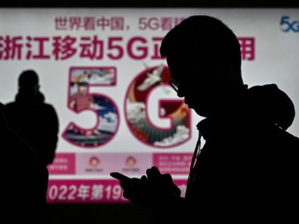 A man looks at his smartphone near an advertisement for 5G internet at the railway station in Hangzhou, Zhejiang province on December 3, 2019. (Photo by HECTOR RETAMAL / AFP) (Photo by HECTOR RETAMAL/AFP via Getty Images)