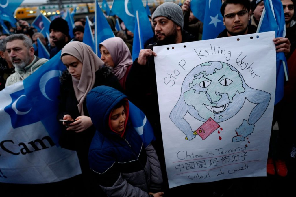 "TOPSHOT - Demonstrators hold a poster reading ""Stop Killing Uyghur - China is Terrorist"" as they take part in a protest outside the Chinese embassy in Berlin on December 27, 2019, to call attention to Chinas mistreatment of members of the Uyghur community in western China. (Photo by John MACDOUGALL / AFP) (Photo by JOHN MACDOUGALL/AFP via Getty Images)"