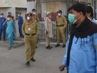 Security personnel (C) and hospital staff wearing facemasks stand outside an hospital entrance in Karachi on February 17, 2020, after a gas leak killed five people and sickened dozens of others in a coastal residential area in Pakistan's port city of Karachi. (Photo by Rizwan TABASSUM / AFP) (Photo by RIZWAN TABASSUM/AFP via Getty Images)